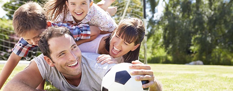 Happy family playing a game of soccer