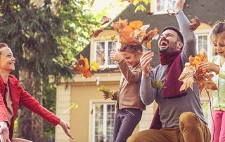 Family celebrating the arrival of fall outside their home