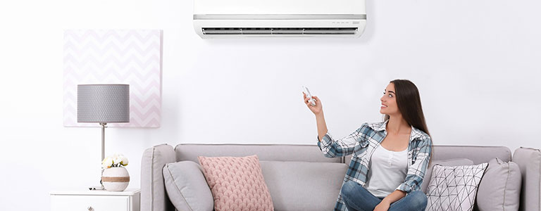 Woman sitting on the sofa and using a remote to adjust the ductless HVAC system