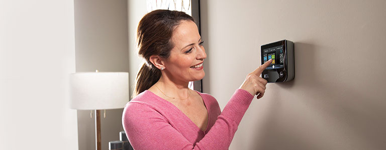 homeowner adjusting her thermostat